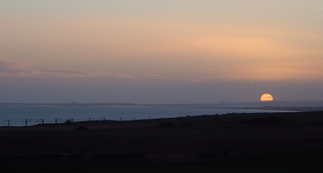 Sun looking coquettish beyond Bamburgh