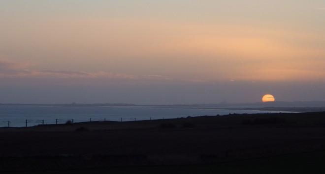 Sun looking coquettish beyond Bamburgh