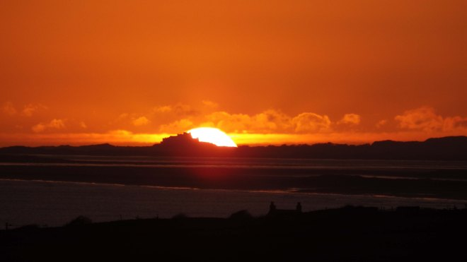 Sun right behind Bamburgh castle