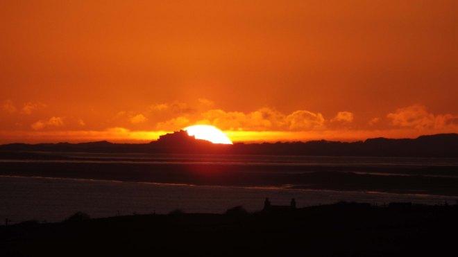 Sun right behind Bamburgh castle