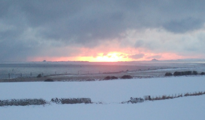 Sunrise over snow between Lindisfarne and Bamburgh castles