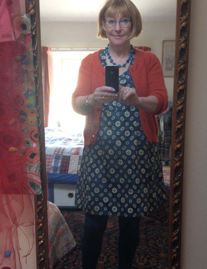 Katherine trying on dress with orange cardi