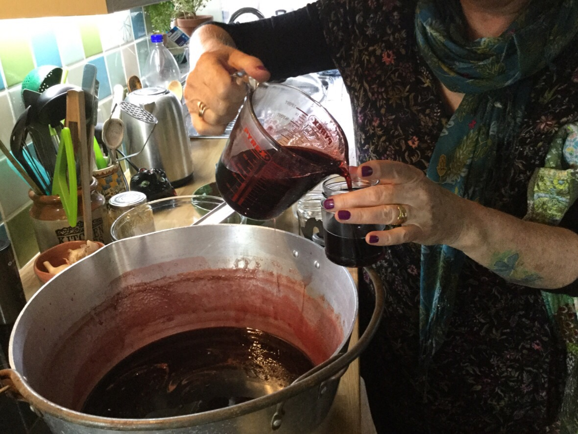 Pouring the jelly mix into the hot jam jars
