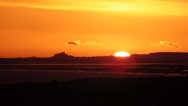 Sunrise past Bamburgh Castle