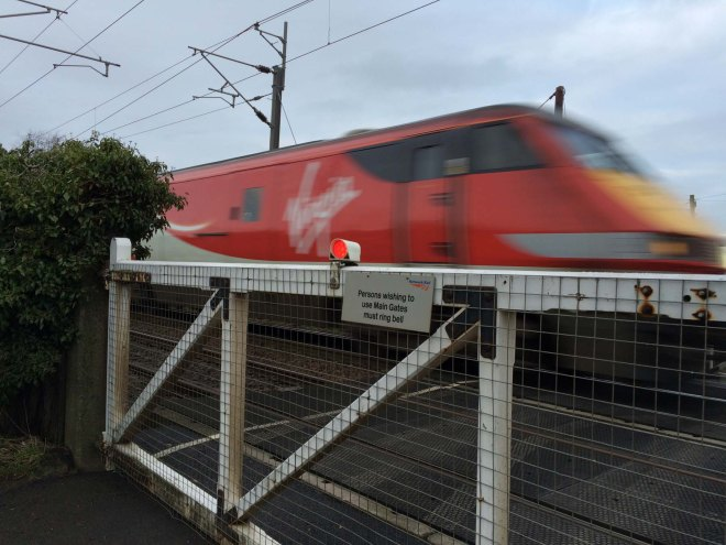 trains rushing past level crossing